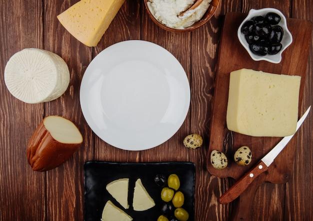 Bovenaanzicht van een lege witte plaat en verschillende soorten kaas met ingelegde olijven en kwarteleitjes gerangschikt op rustieke tafel