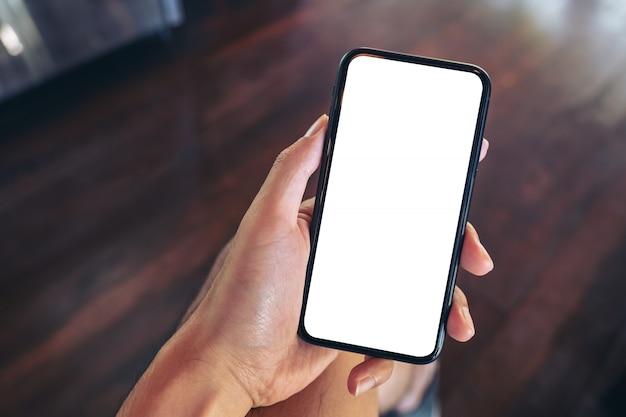 Bovenaanzicht van een man die een zwarte mobiele telefoon met een leeg wit scherm vasthoudt