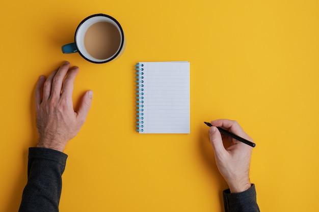 Bovenaanzicht van een man klaar om te schrijven in zijn lege notitieblok met zwarte stift