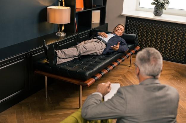 Bovenaanzicht van een man van middelbare leeftijd liggend op de bank in gesprek met een mannelijke psychotherapeut in zijn kantoor
