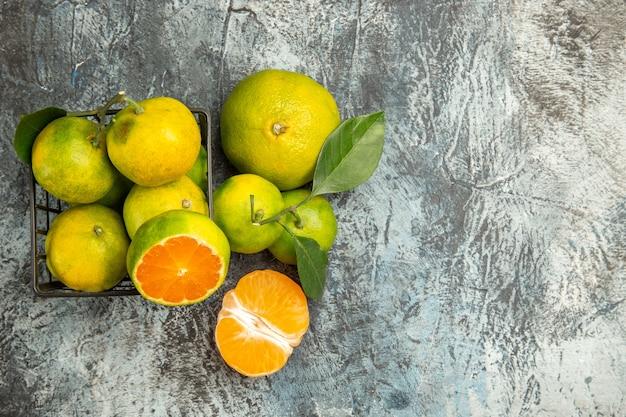 Bovenaanzicht van een mand met verse groene mandarijnen in tweeën gesneden en gepelde mandarijn aan de rechterkant van grijze achtergrond