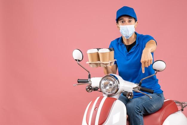 Bovenaanzicht van een mannelijke bezorger met een masker met een hoed die op een scooter zit en bestellingen aflevert die naar beneden wijzen op een perzikachtergrond