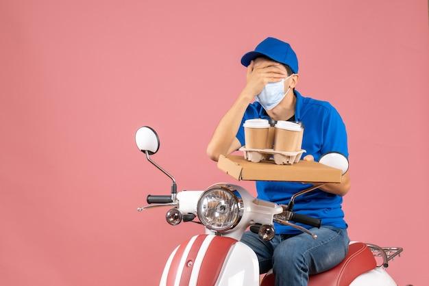 Bovenaanzicht van een mannelijke bezorger met een masker met een hoed die op een scooter zit en bestellingen aflevert die zijn oog sluiten