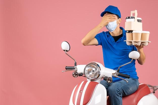 Bovenaanzicht van een mannelijke bezorger met een masker met een hoed op een scooter die bestellingen aflevert en zijn oog sluit op de perzikachtergrond peach