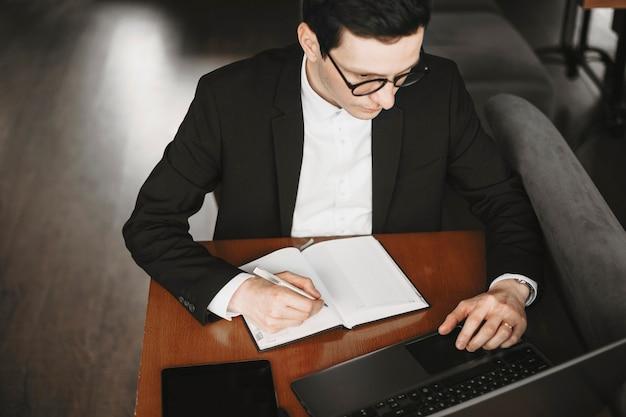 Bovenaanzicht van een mannenhand die in een notitieblok schrijft en op een laptop werkt terwijl hij op een tafel zit.
