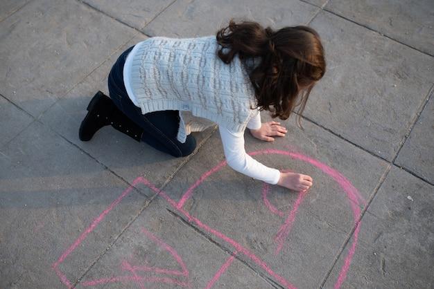 Bovenaanzicht van een meisje dat met krijt op de straatvloer schildert om te hinkelen
