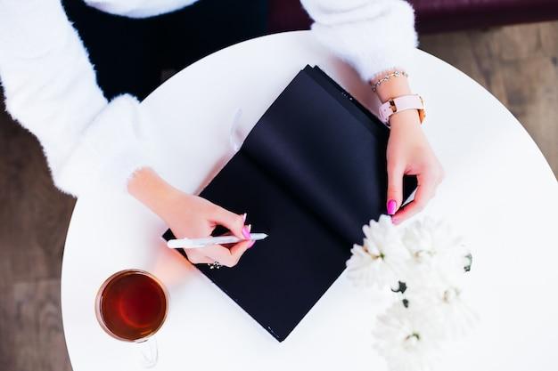 Bovenaanzicht van een meisje in een café dat aan de tafel zit en schrijft in een notitieblok met zwarte pagina's