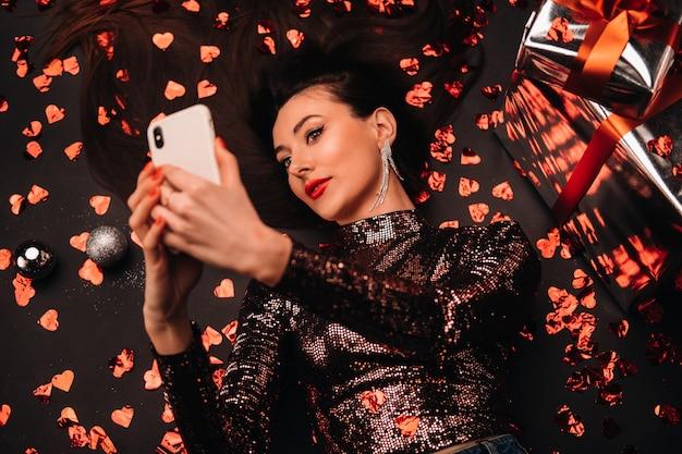 Bovenaanzicht van een meisje in glanzende kleding op de vloer liggen in confetti in de vorm van harten en een selfie nemen.