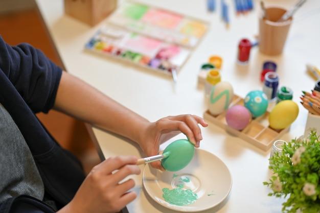 Bovenaanzicht van een meisje paaseieren met poster kleur schilderen op de tafel in de woonkamer