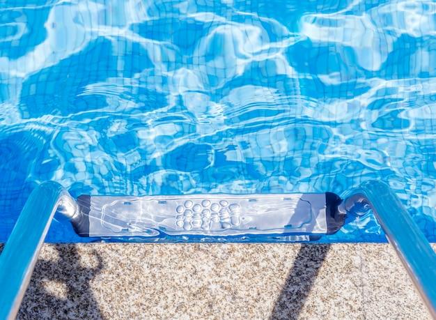 Bovenaanzicht van een metalen ladder met reling in een zwembad met tegelvloer