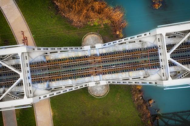 Bovenaanzicht van een metalen spoorbrug passeren door de rivier in de buurt van het park.