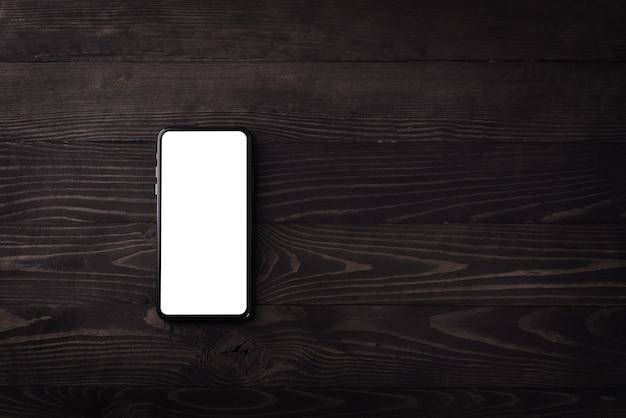 Bovenaanzicht van een moderne smartphone op zwarte houten tafel close-up
