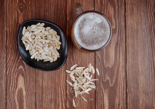 Bovenaanzicht van een mok bier en een flesje bier met zoute snack zonnebloempitten in een kom op rustiek hout
