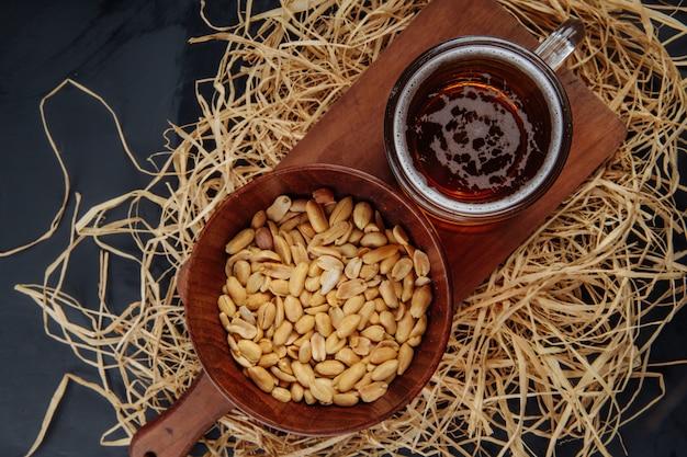 Bovenaanzicht van een mok bier en pinda's in een kom op houten bord op stro op zwarte jpg