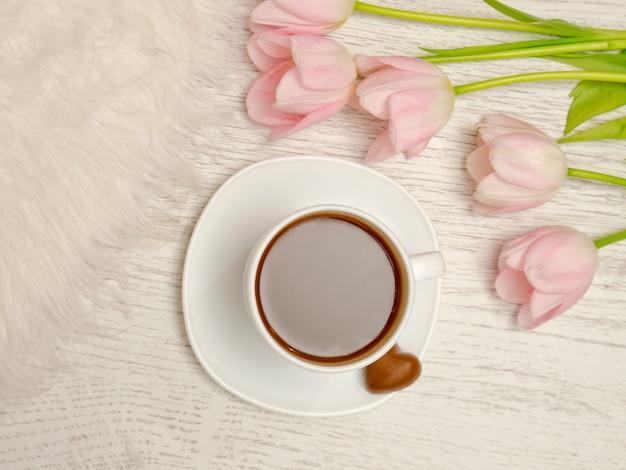 Bovenaanzicht van een mok koffie en een boeket tulpen