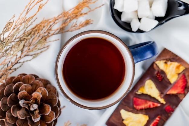 Bovenaanzicht van een mok thee en dennenappel met chocoladereep op wit
