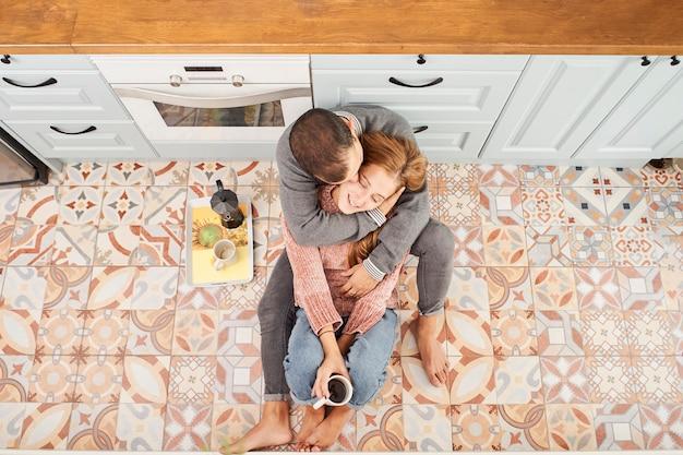 Bovenaanzicht van een mooi jong koppel koffie drinken zittend op de keukenvloer thuis
