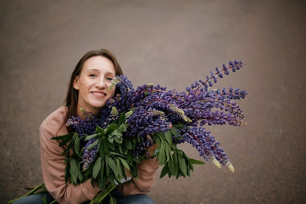 Bovenaanzicht van een mooi meisje met een enorm boeket wilde violette lupines, gekleed in vrijetijdskleding onderweg