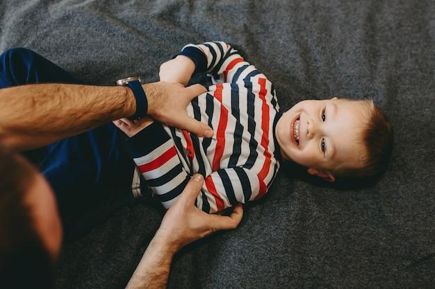 Bovenaanzicht van een mooie gelukkige jongen, leunend op een bed, lachen tijdens het spelen met zijn vader in de ochtend.