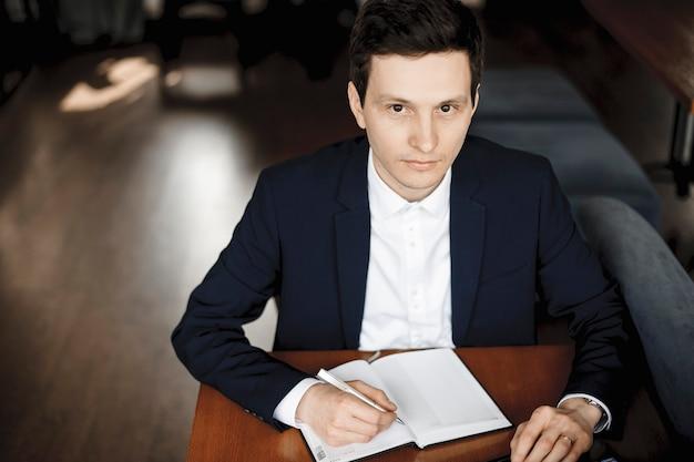 Bovenaanzicht van een mooie jonge blanke man die in een notitieboekje schrijft terwijl hij aan een bureau zit, gekleed in pak en kijkt naar de camera die lacht.