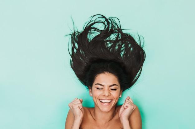 Bovenaanzicht van een mooie jonge topless brunette vrouw met lang haar tot over blauw