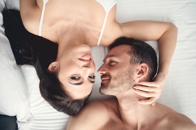 Bovenaanzicht van een mooie jonge vrouw die in bed ligt dicht bij haar liefhebbende echtgenoot