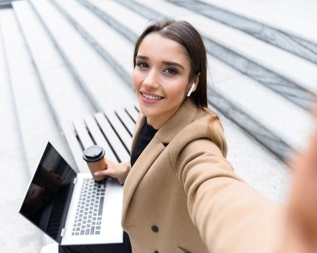 Bovenaanzicht van een mooie jonge vrouw met een herfstjas die een laptop gebruikt terwijl ze op een bankje zit, een koffiekopje drinkt, een selfie maakt