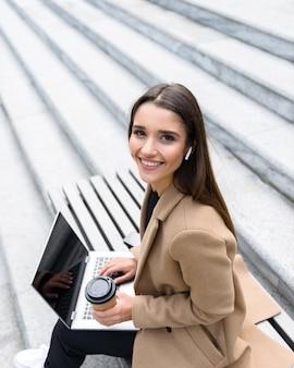 Bovenaanzicht van een mooie jonge vrouw met een herfstjas die een laptop gebruikt terwijl ze op een bankje zit en een koffiekopje drinkt