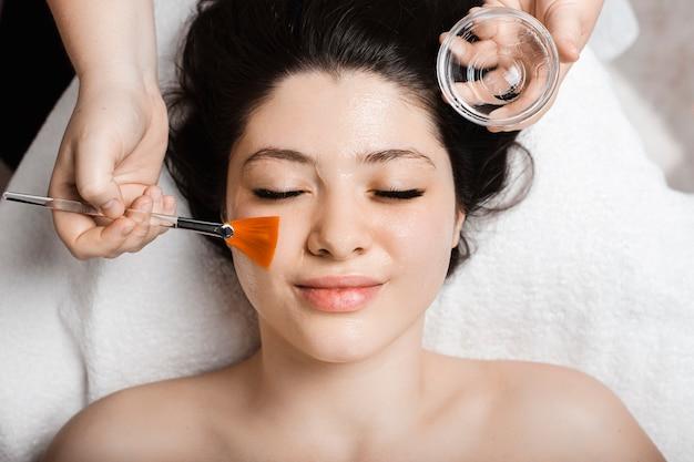 Bovenaanzicht van een mooie vrouw die met gesloten ogen leunt terwijl schoonheidsspecialist een huidverzorgingsmasker op haar gezicht toepast.