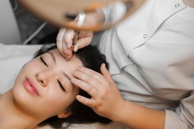 Bovenaanzicht van een mooie vrouw die microdermabrasie procedure op haar gezicht in spa wellness-centrum doet.