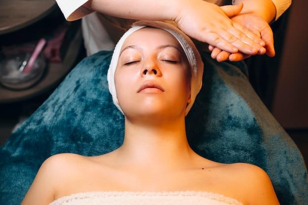 Bovenaanzicht van een mooie vrouw die op een kuuroordbed leunt met gesloten ogen die gezichtsschil in een wellnesskuuroord doen.