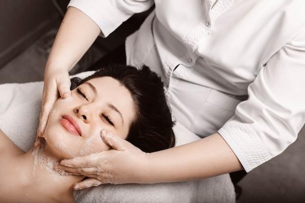 Bovenaanzicht van een mooie vrouw leunend op een spa-bed met gesloten ogen glimlachend terwijl het hebben van huidverzorging anti leeftijd massage met schuim door een schoonheidsspecialist.