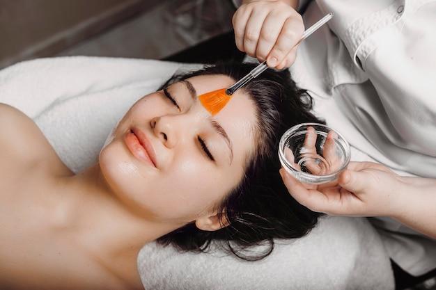 Bovenaanzicht van een mooie vrouw met huid routine masker hydratatie in een wellnesscentrum.