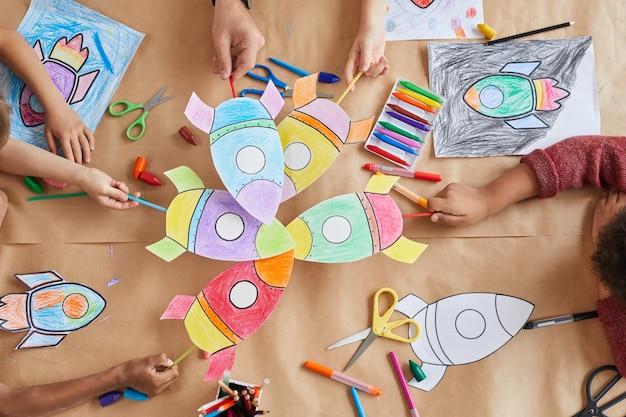 Bovenaanzicht van een multi-etnische groep kinderen die foto's van ruimteraketten vasthouden terwijl ze genieten van kunst- en ambachtlessen in de kleuterschool of het ontwikkelingscentrum