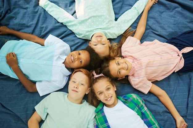 Bovenaanzicht van een multi-etnische groep kinderen liggend in cirkel op deken buitenshuis