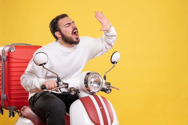 Bovenaanzicht van een nerveuze jonge kerel die op een motorfiets zit met een koffer erop en iemand belt op een geïsoleerde gele achtergrond