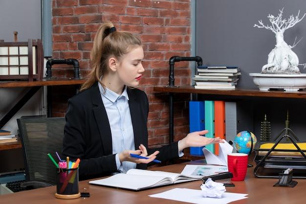 Bovenaanzicht van een nieuwsgierige dame die aan een tafel zit en zich zorgvuldig op iets concentreert op kantoor