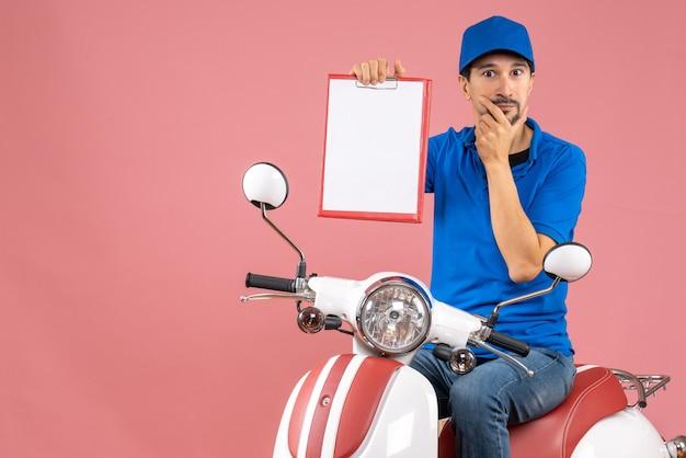 Bovenaanzicht van een nieuwsgierige koeriersman met een hoed die op een scooter zit en een document vasthoudt op een pastelkleurige perzikachtergrond