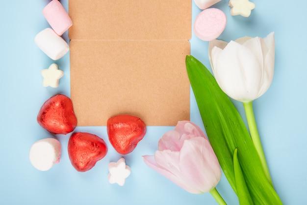 Bovenaanzicht van een open bruine papieren wenskaart met verspreide marshmallows en hartvormige chocoladesuikergoed in rode folie met roze kleurentulpen op blauwe tafel
