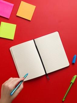 Bovenaanzicht van een open lege rode notebook in het midden