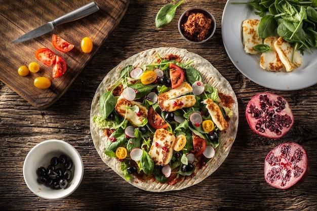 Bovenaanzicht van een open vegetarische tortilla met salade, radijs, cherrytomaatjes, olijven, granaatappel en gegrilde haloumi-kaas.
