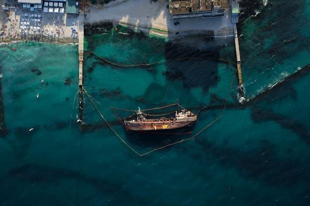 Bovenaanzicht van een oude tanker die aan de grond liep en omviel