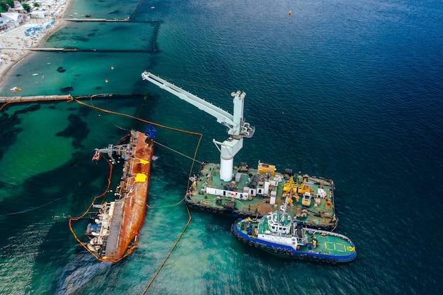 Bovenaanzicht van een oude tanker die aan de grond liep en op de kust bij de kust viel