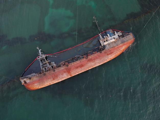 Bovenaanzicht van een oude tanker die aan de grond liep en op de kust bij de kust viel.