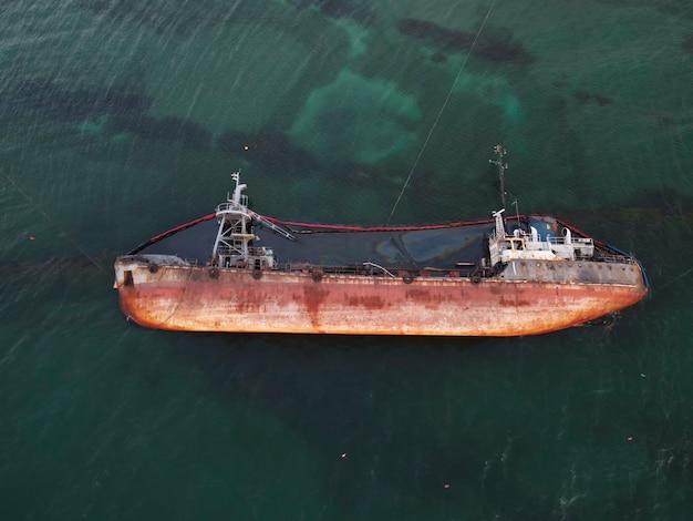 Bovenaanzicht van een oude tanker die aan de grond liep, kantelde en de kust vervuilde met gemorste olie. ecologische ramp.