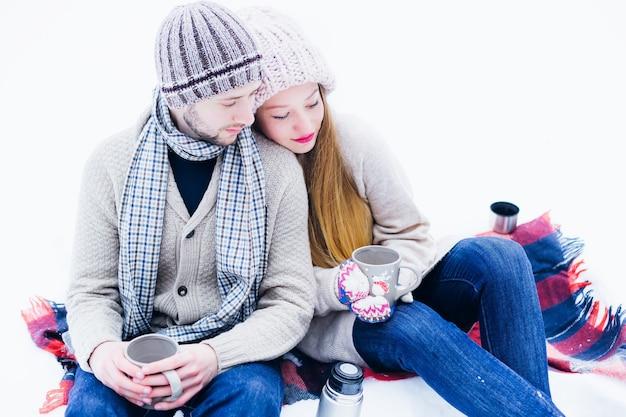 Bovenaanzicht van een paar dat in warme kleren in de sneeuw zit