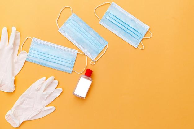 Bovenaanzicht van een paar medische latexhandschoenen en chirurgisch oorlusmasker op oranje achtergrond.