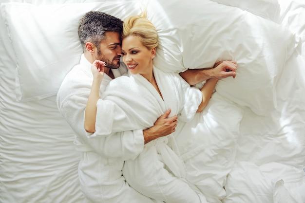 Bovenaanzicht van een paar van middelbare leeftijd verliefd in badjassen op huwelijksreis liggend in een bed en knuffelen.
