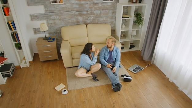 Bovenaanzicht van een paar vechten tijdens het spelen van videogames op de vloer van hun gezellige huis