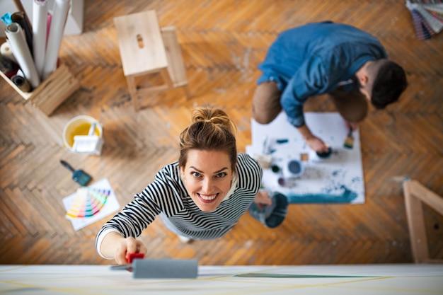 Bovenaanzicht van een paar volwassenen die de muur binnenshuis schilderen, verhuizing en doe-het-zelf concept.